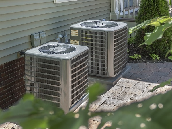 2 hvac units outside of home on stone walkway