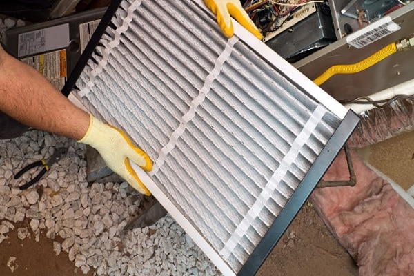 Filter replacement attic furnace with gloved hands and insulation