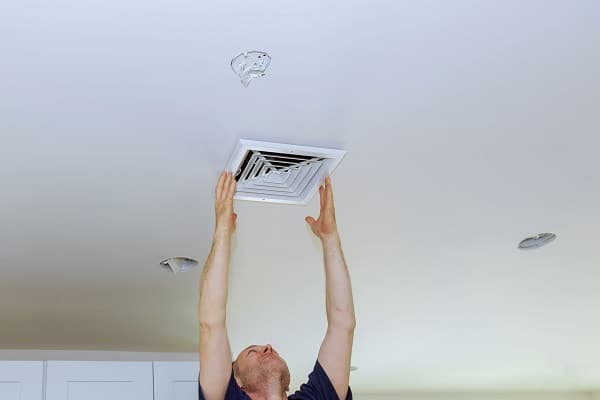 Installing new white air conditioning vent closeup ceiling mounted air conditioner