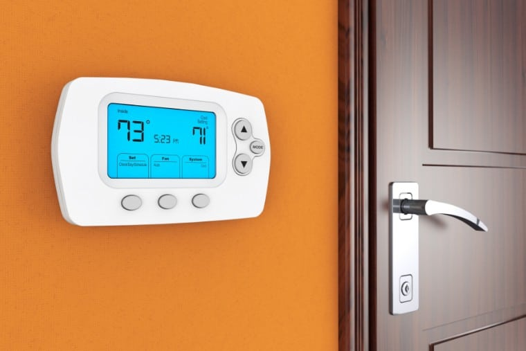 Thermostat on orange wall.