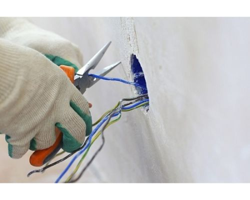 two gloved hands using pliers on wire from wall